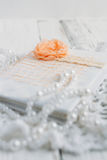 Vintage notebook on white table. Vintage handmade Notepad on a white table cloth and beads from pearls Stock Photo