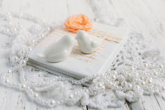 Vintage notebook on white table. Vintage handmade Notepad on a white table cloth and beads from pearls Stock Image