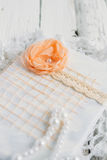 Vintage notebook on white table. Vintage handmade Notepad on a white table cloth and beads from pearls Royalty Free Stock Image