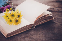 Vintage novel books with bouquet of flowers on old wood background Stock Photo