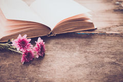 Vintage novel books with bouquet of flowers on old wood background Stock Image