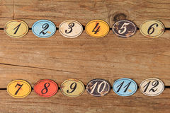 Vintage number buttons. Vintage oval shaped wooden number buttons on a weather wooden table Royalty Free Stock Images