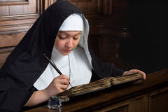 Vintage nun with book. Vintage scene of a young nun writing in an ancient book stock photo