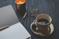 Vintage objects and a cup of coffee on the wooden table. Atmosphere of relax, dream, art or work. Notebook, pen, gold chain, and candles on the table royalty free stock image
