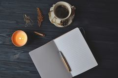 Vintage objects and a cup of coffee on the wooden table. Atmosphere of relax, dream, art or work. Notebook, pen, gold chain, and candles on the table royalty free stock photos