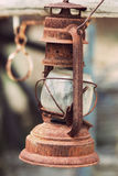 Vintage oil lamp. View of a rusty kerosene lamp  hanging on a western carriage Stock Image