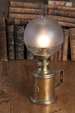 Vintage oil lamp with books. Lit vintage oil lamp standing on a table with old books in the background Stock Photos