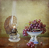 Vintage oil lamp and grapes Stock Image