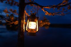 Free Vintage Oil Lamp Hanging On A Tree. Beautiful View Of Dark Forest And Lake At Night. Hiker, Travel, Outdoor Concept Royalty Free Stock Image - 164463546