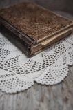 Vintage old book and lace fabric on the old wood Royalty Free Stock Image