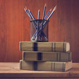 Vintage old book with pencils on wooden table. Over retro wooden background Royalty Free Stock Images