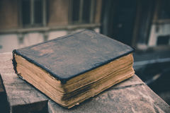 Vintage old book on stone, grunge textured cover. Retro styled image with blurred background. Royalty Free Stock Images