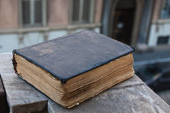 Vintage old book on stone, grunge textured cover. Retro styled image with blurred background. Stock Photography