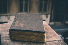 Vintage old book on stone, grunge textured cover. Retro styled image with blurred background. Stock Image
