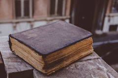 Vintage old book on stone, grunge textured cover. Retro styled image with blurred background. Stock Photos