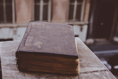 Vintage old book on stone, grunge textured cover. Retro styled image with blurred background. Stock Photo