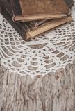 Vintage old books and lace fabric on the old wood Stock Images