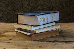 Vintage old books on wooden deck table with soil wall Royalty Free Stock Image