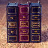 Vintage old books on wooden deck tabletop against grunge wall Royalty Free Stock Images