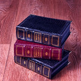 Vintage old books on wooden deck tabletop against grunge wall.  Stock Photo