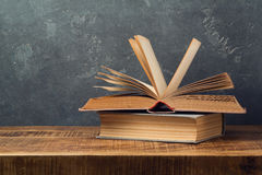 Vintage old books on wooden table over blackboard background. Education Stock Images