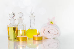 Vintage old bottles of aromatic oils with burned candles, flowers  and white towel on glossy white table on white background Royalty Free Stock Images