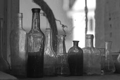Vintage old bottles BW. Close up of a few vintage old bottles in an old window. Artistic Still Life photo. Black and White royalty free stock photos