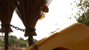 Vintage Old Brooms Chained with Yellow Plastic Chair stock image