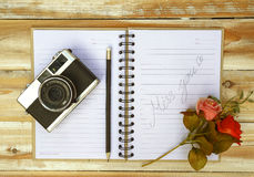 The vintage old camera with book and pencil on the wooden Royalty Free Stock Images