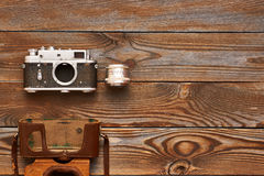 Vintage old camera and lens on wooden background Stock Image