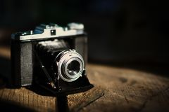 Vintage old camera on a wooden table. Retro style, nostalgia - V. Intage effect photo Stock Photography