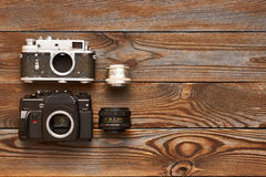 Vintage old cameras and lenses on wooden background Royalty Free Stock Photo