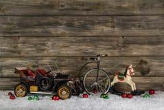 Vintage: old children toys for a christmas decoration - car, hor. Old antique children toys of wood and tin for christmas decoration on wooden rustic background Stock Image