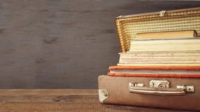 Vintage old classic travel leather suitcases with stack of old books and albums. Travel luggage concept. Retro toning filtered moc royalty free stock images