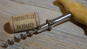 Vintage old corkscrew and rolling wine cork with inscription bottled in France stock footage