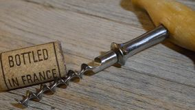 Vintage old corkscrew and rolling wine cork with inscription bottled in France. Vintage old corkscrew and wine cork with inscription bottled in France stock footage