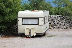 Vintage old dilapidated camper trailer parked in backyard on gravel surface next to improvised stone wall surrounded with dense. Trees in background on warm stock photography