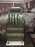 Vintage and old fashion cash register machine. In the back a very vintage photo Royalty Free Stock Photography