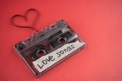 Vintage old film music cassette on a trendy pink red background with the inscription love song, background music, music lovers
