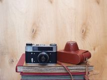 Vintage old film photo-camera with leather case on wooden background Stock Photography