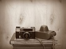 Vintage old film photo-camera and photo-albums on wooden background, sepia vignette Stock Photo