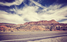 Vintage old film stylized picture of a scenic desert road. Royalty Free Stock Image