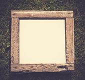 Vintage old grunge wood frame on grass, empty space for text. Stock Photos