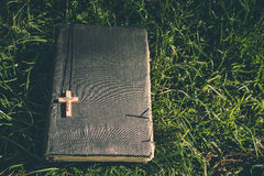 Vintage old holy bible book, grunge textured cover with wooden christian cross. Retro styled image on grass background. Stock Image