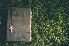 Vintage old holy bible book, grunge textured cover with wooden christian cross. Retro styled image on grass background. Stock Images