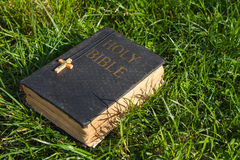 Vintage old holy bible book, grunge textured cover with wooden christian cross. Retro styled image on grass background. Royalty Free Stock Photography