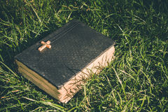 Vintage old holy bible book, grunge textured cover with wooden christian cross. Retro styled image on grass background. Royalty Free Stock Photos