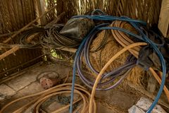 Vintage Old Hoses on Dirty Concrete Ground - Hay, Wood and Plastic Sheet in Messy Chicken Coop - Rural Vietnam royalty free stock photos