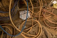 Vintage Old Hoses on Dirty Concrete Ground - Hay, Wood and Rusty Knife in Messy Chicken Coop - Rural Vietnam royalty free stock photography