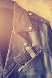 Vintage old leather jacket with gun in the pocket on grain paper background Stock Image